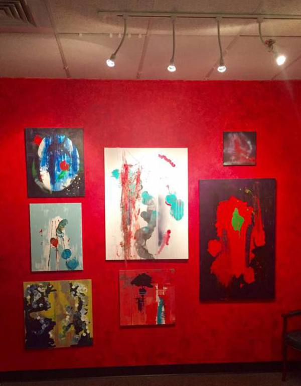 View of paintings on red wall